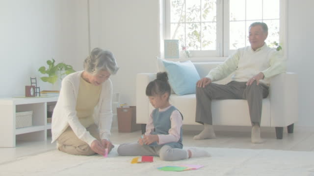 grandmother and granddaughter folding paper into figures - 祖母点の映像素材/bロール
