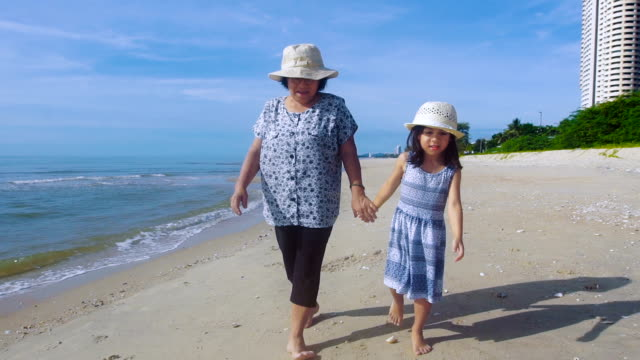 Grandmother And Granddaughter Holding Hands Walking Along Beach