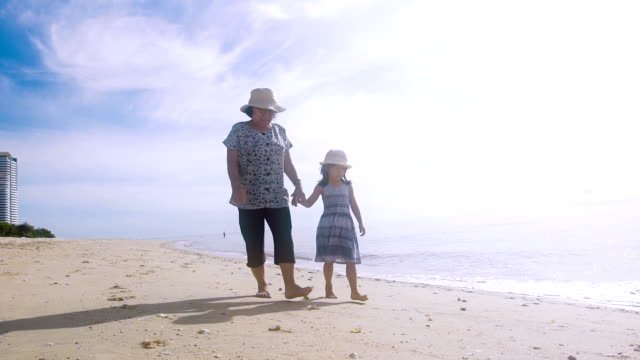 grandmother and granddaughter holding hands walking along beach - barefoot video stock e b–roll