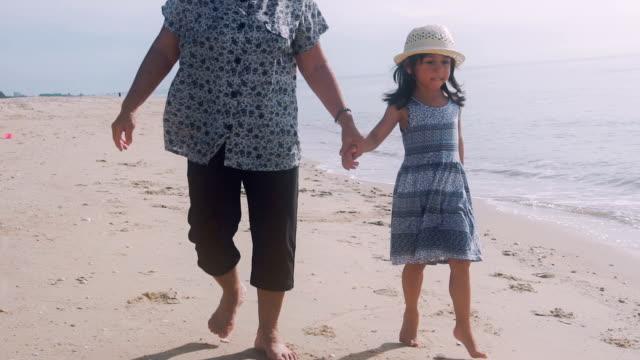 Großmutter und Enkelin Händchenhalten Strand entlang spazieren