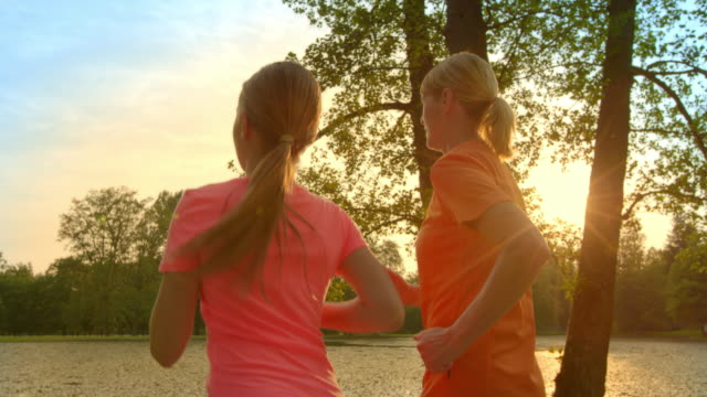 SLO MO TS Grandmother and granddaughter jogging at sunset