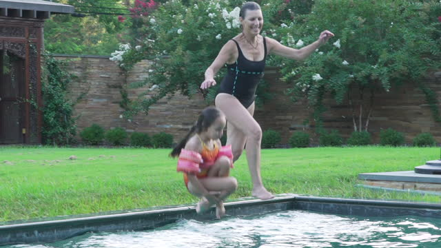grandmother and granddaughter jumping into swimming pool - swimming costume stock videos and b-roll footage