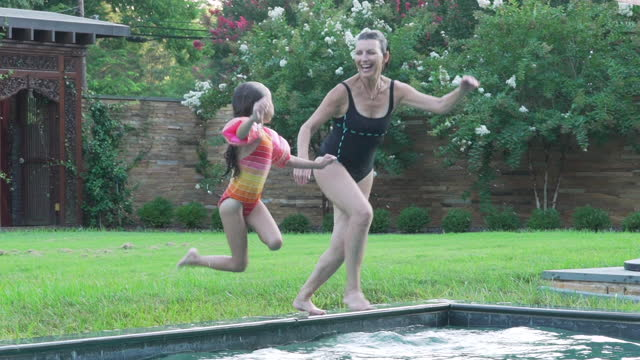 Grandmother and Granddaughter Jumping into Swimming Pool