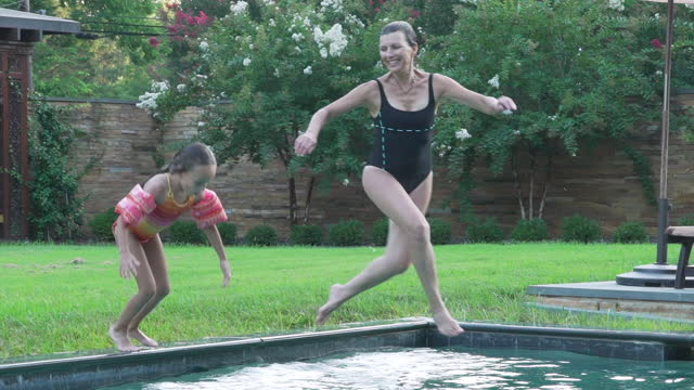 vídeos y material grabado en eventos de stock de grandmother and granddaughter jumping into swimming pool - traje de baño de una pieza