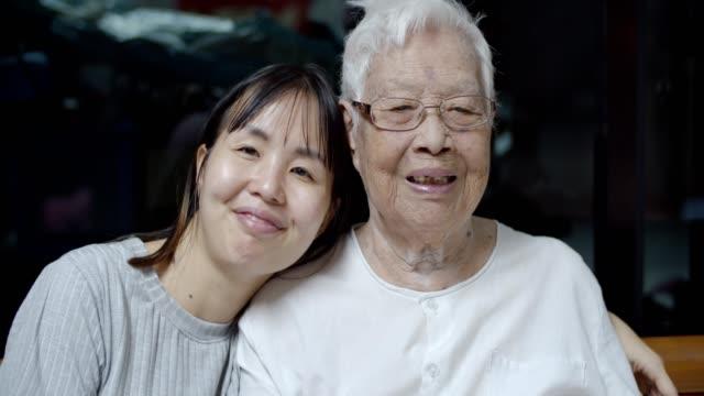 großmutter und enkelin blick in die kamera zu hause - großeltern stock-videos und b-roll-filmmaterial