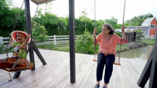 vídeos y material grabado en eventos de stock de abuela y nieta jugando en el swing de patio de recreo - abuelos