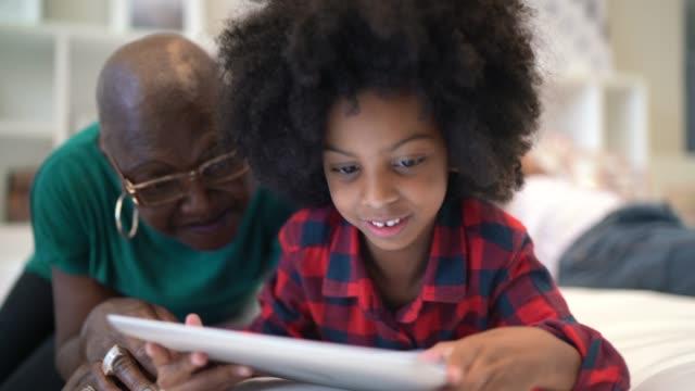 vídeos de stock, filmes e b-roll de avó e neta que jogam com tabuleta digital - lendo