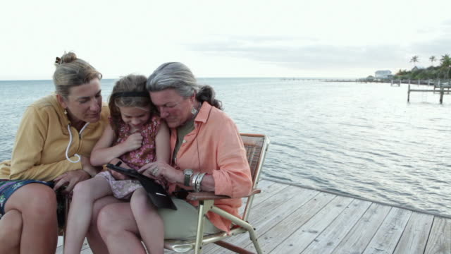 MS PAN Grandmother and granddaughter playing with ipad on dock / Florida Keys, Florida, United States