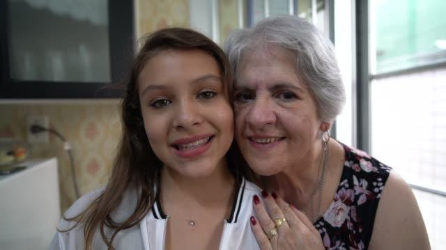 großmutter und enkelin porträt zu hause - gesichtsausdruck stock-videos und b-roll-filmmaterial