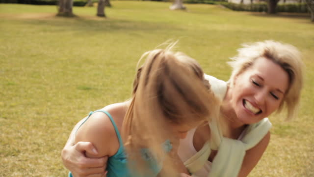 grandmother and granddaughter running and hugging in park. - 少於10秒 個影片檔及 b 捲影像