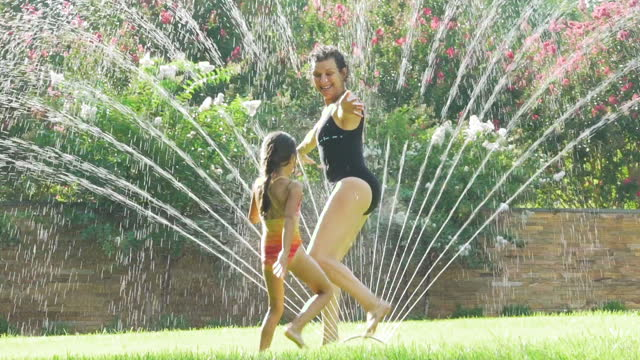 Grandmother and Granddaughter Running Through Water Sprinkler