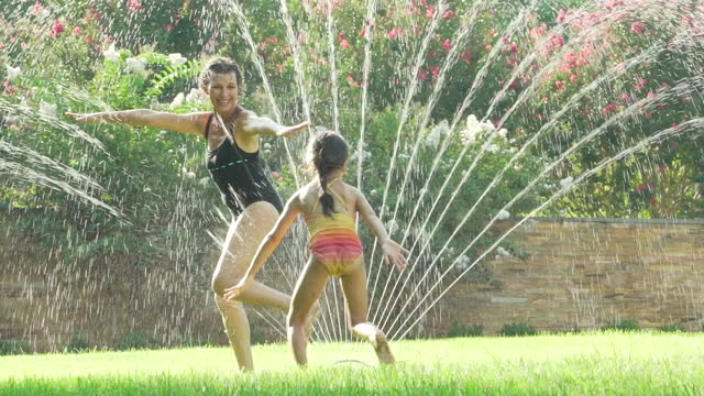 grandmother and granddaughter running through water sprinkler - grandchild stock videos & royalty-free footage