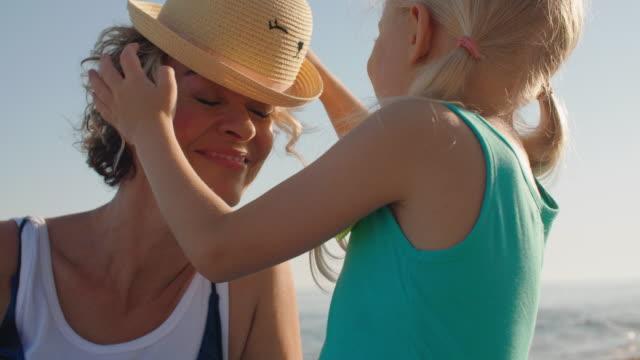 vídeos y material grabado en eventos de stock de grandmother and granddaughter sitting on beach playing with hats - nieta