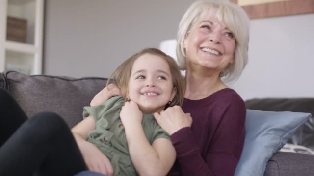a grandmother and granddaughter snuggle together on the couch. - cosy stock videos & royalty-free footage