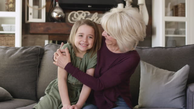 a grandmother and granddaughter snuggle together on the couch. - affectionate stock videos & royalty-free footage