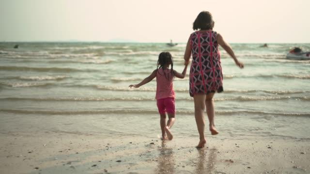 vídeos y material grabado en eventos de stock de abuela y nieta salpicando el agua de mar el uno al otro en la playa - dos personas