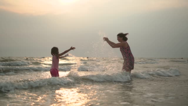 grandmother and granddaughter splashing the water on each other in the sea - grandparents stock videos & royalty-free footage