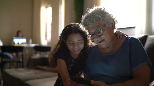 grandmother and granddaughter using mobile phone at home - leisure activity stock videos & royalty-free footage