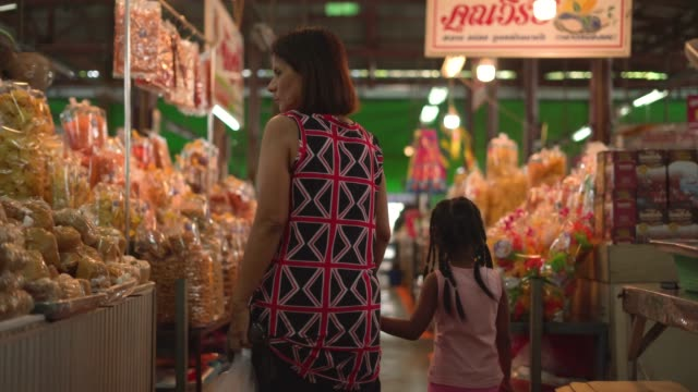 grandmother and granddaughter walking in the market - tracking shot stock videos & royalty-free footage