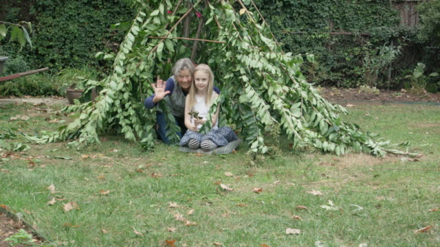 Grandmother and Granddaughter Wave from Garden Teepee