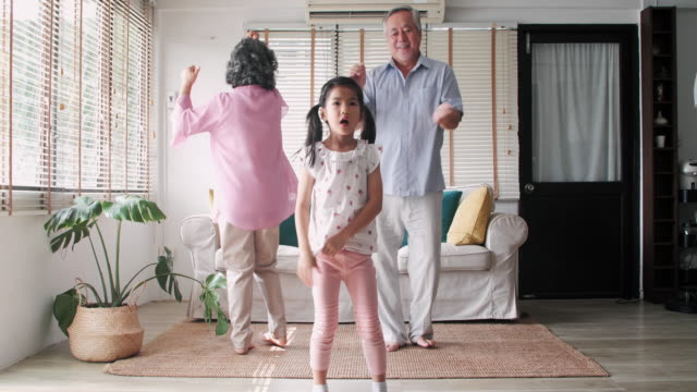 grandmother and grandfather together with their granddaughters dancing in home.leisure, holidays, fun and people concept - happy family dancing at summer party in home. - grandchild stock videos & royalty-free footage