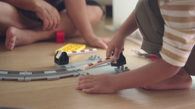 mormor och barnbarn leker med leksaker tillsammans hemma. - golv bildbanksvideor och videomaterial från bakom kulisserna