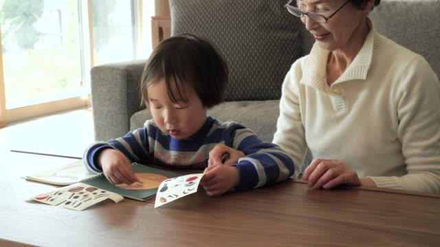 おばあちゃんが、孫の楽しいリビングルーム」 - 大家族点の映像素材/bロール