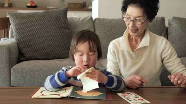 おばあちゃんが、孫の楽しいリビングルーム」 - 祖母点の映像素材/bロール