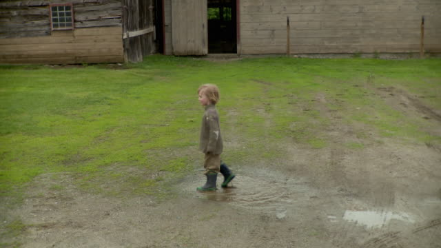 ms pan grandmother and grandson (2-3) jumping in puddle / stowe, vermont, usa    - farmhouse stock videos & royalty-free footage