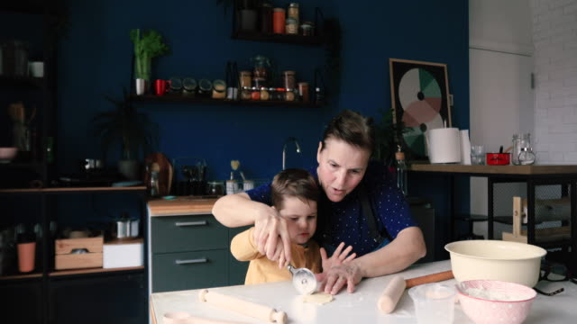 grandmother and grandson kneading yeast dough - grandson stock videos & royalty-free footage
