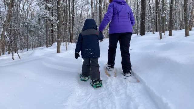 Grandmother and Grandson Snowshoeing and Exploring Forest on Hiking Trail In Winter
