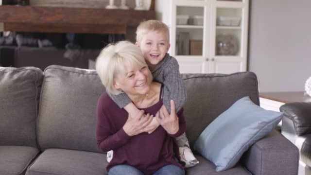 a grandmother and grandson snuggle together on the couch. - cosy stock videos & royalty-free footage