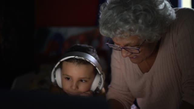 vidéos et rushes de grand-mère et petit-fils utilisant l'ordinateur portatif à la maison - septuagénaire