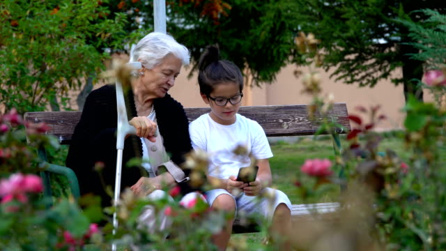 grandmother and grandson using smart phone in public park - portable information device stock videos & royalty-free footage