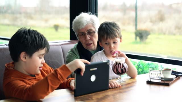 großmutter und enkel suchen digitales tablet in einem café - clip stock-videos und b-roll-filmmaterial