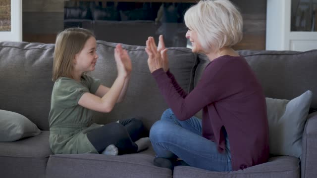a grandmother and her granddaughter clap hands and play together on the couch. - granddaughter stock videos & royalty-free footage