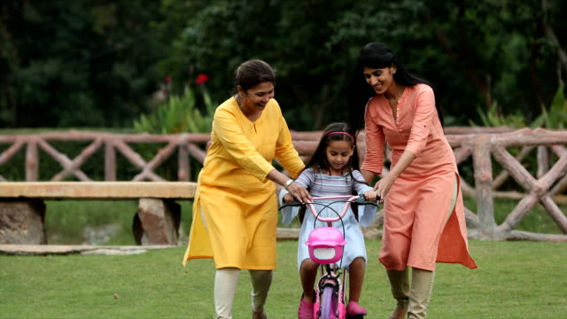 MS ZI Grandmother and mother teaching girl to ride bicycle in backyard / Delhi, India