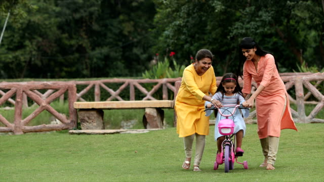 ms zi grandmother and mother teaching girl to ride bicycle in backyard / delhi, india - teaching stock-videos und b-roll-filmmaterial
