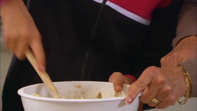 cu, zo, grandmother assisting girl (10-11) mixing cookie dough in kitchen - 10 11 år bildbanksvideor och videomaterial från bakom kulisserna