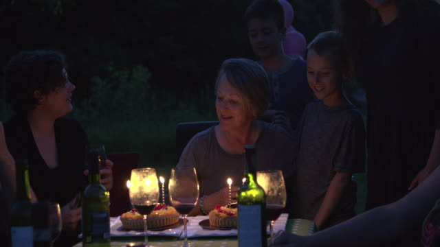 grandmother birth party big family outdoor at night with cake and candles - gazebo stock videos & royalty-free footage