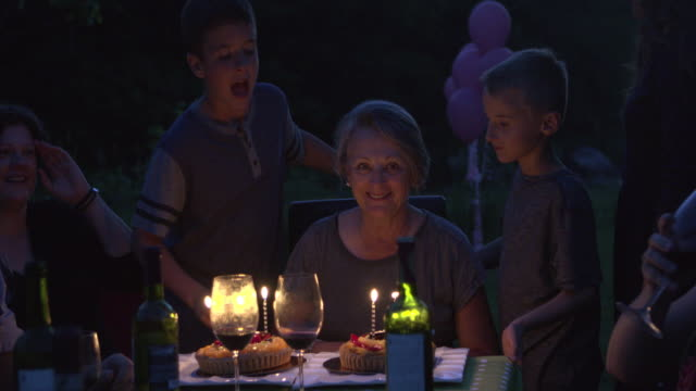 vídeos de stock e filmes b-roll de grandmother birth party big family outdoor at night with cake and candles - avó