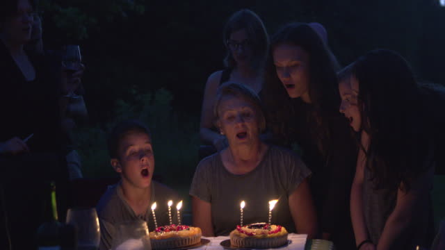 Grandmother Birth Party Big Family Outdoor at Night with Cake and Candles