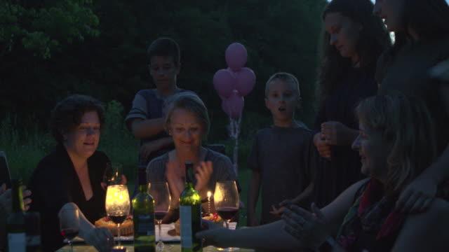 vídeos y material grabado en eventos de stock de partido de nacimiento de la abuela familia grande al aire libre en la noche con torta y velas - abuela