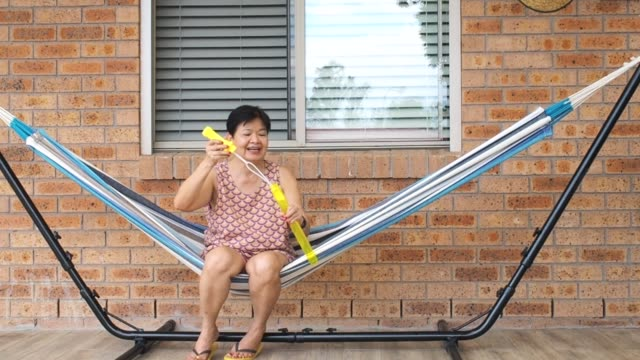 grandmother (grandma) blowing bubbles while her grandchildren are trying to catch it - 60 64 years stock videos & royalty-free footage