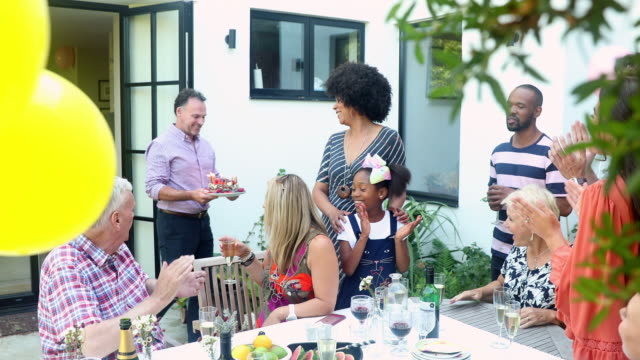 vídeos de stock, filmes e b-roll de grandmother blowing out birthday cake candles at garden patio party with multi generation family - 40 49 anos