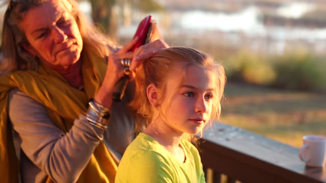 Grandmother brushing her 8 year old daughter's hair on porch