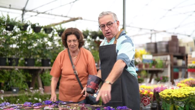 grandmother buying flowers at market - fioraio negozio video stock e b–roll