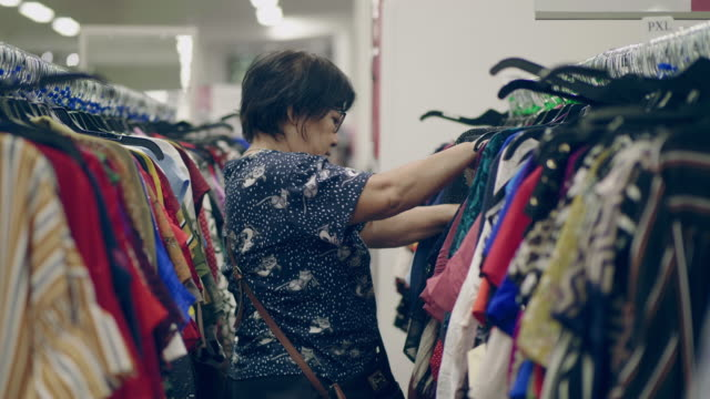 grandmother chooses clothes in shopping mall - fashionable stock videos & royalty-free footage