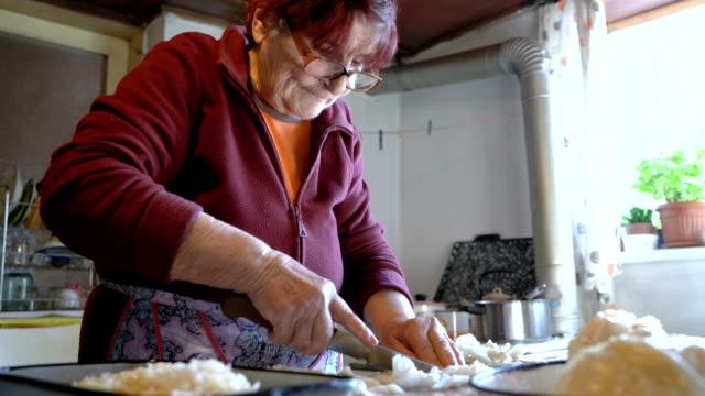 stockvideo's en b-roll-footage met grootmoeder koken in haar dorpshuis - eten koken