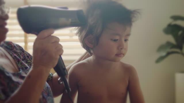 おばあちゃんは家で男の子をドレスアップ。 - 電化製品点の映像素材/bロール